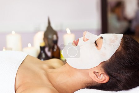 Prettyl woman with facial mask at beauty salon. Spa treatment