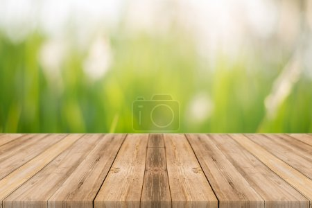 Wooden board empty table blur trees in forest - can be used for display or montage your products. spring season. vintage filtered image.