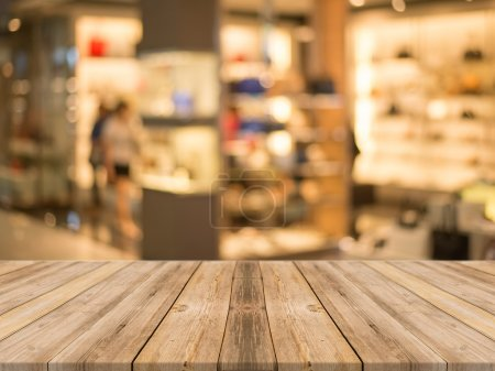 Wooden board empty table in front of blurred background. Perspective brown wood over blur store in mall - can be used for display or montage your products. vintage filtered image.