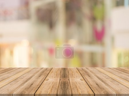 Wooden board empty table in front of blurred background. Perspective brown wood over blur store in mall - can be used for display or montage your products.