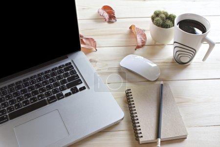 Photo pour Une tasse de café, ordinateur portable, souris, carnet, crayon et cactus sur table en bois - image libre de droit