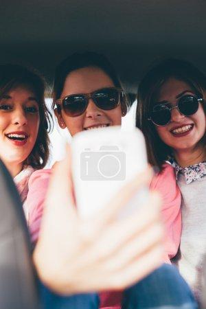 three friends taking photos