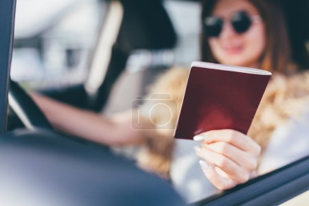 Photo for Beautiful young woman showing her passport or driving license - Royalty Free Image