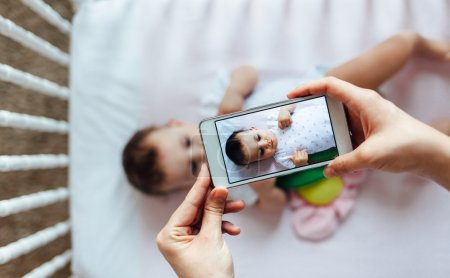 Photo for Happy mother taking a picture of her baby girl in crib with smart phone - Royalty Free Image
