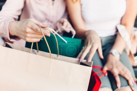 Women opening shopping bags