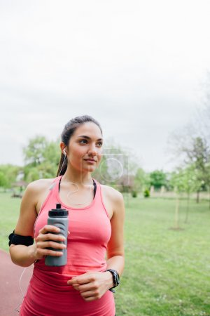 Sport woman drinking water after exercise
