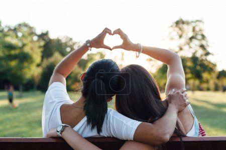 Photo for Mom and daughter forming a heart with their hands while embracing on a park bench - Royalty Free Image
