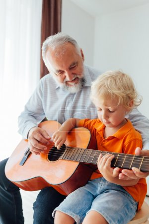 Grandpa learning his grandson to play guitar