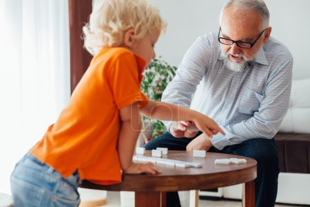 Grandfather teaches his grandson to play dominoes