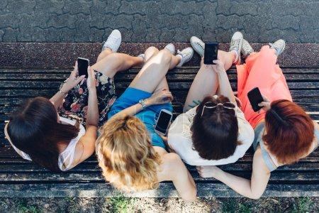 Photo pour Vue aérienne d'une adolescente utilisant des téléphones mobiles - image libre de droit