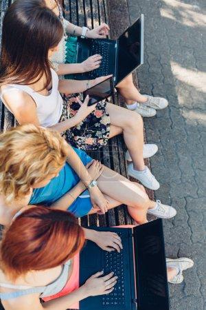 Photo pour Gros plan de copines utilisant les nouvelles technologies sur un banc de parc - image libre de droit