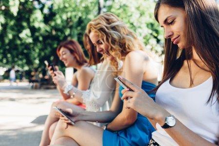 Photo pour Belles adolescentes assises sur un banc de parc et utilisant des téléphones mobiles - image libre de droit