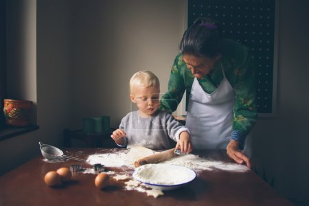 Little baker with grandmother preparing Christmas cookies