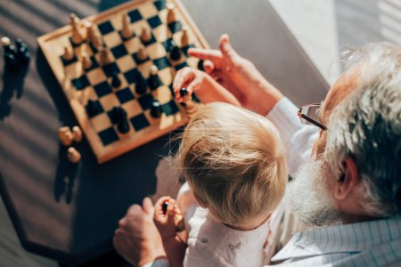 Grandfather teaches his grandson to play chess