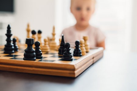Little chess player thinking in the background