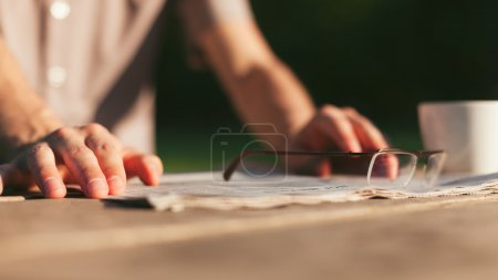 Man reading the newspaper outdoors