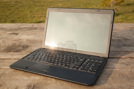 Laptop on Wooden Table at Sunset