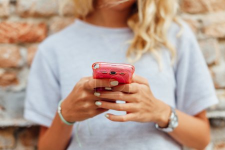 Closeup of blonde uses her smartphone