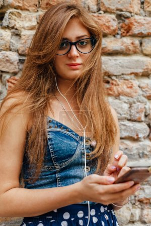 Beautiful brunette listens to music from your smartphone