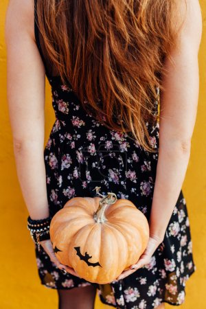 Closeup of girl holds Halloween pumpkin with bats concept