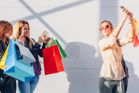 Beautiful girls with shopping bags taking a selfie with their sm
