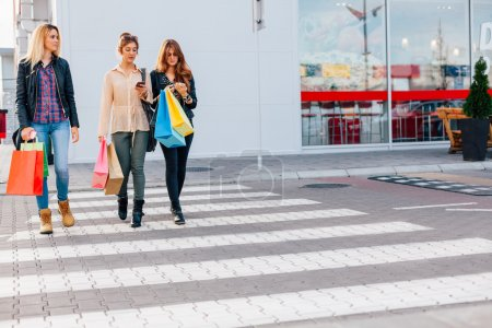 Three girls hold shopping bags and cross the street with copy sp
