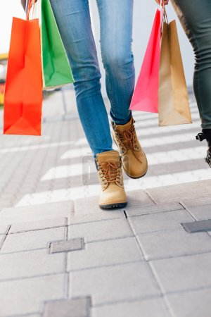 Closeup of girls hold colorful shopping bags and cross the street