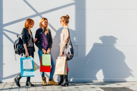 Three girls with colorful bags after shopping with copy space on