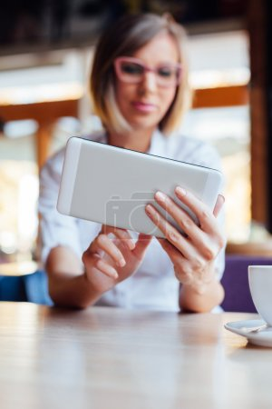 Woman using free internet on new tablet in a cafe