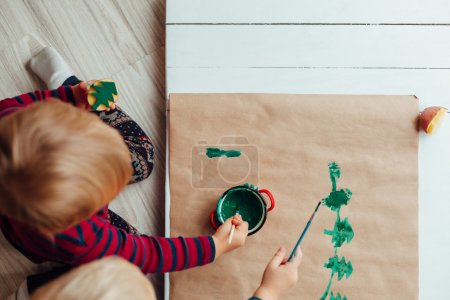 Children drawing a Christmas tree on classic paper