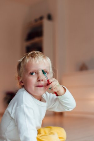 Photo for Little painter holding brush and looking at something - Royalty Free Image