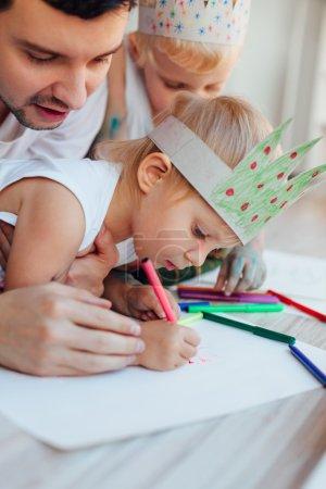 Dad teaches children to draw
