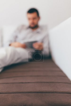 Man in background using Tablet on The Bed