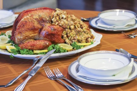 Garnished roasted turkey on fall festival decorated table with horn of plenty and red wine