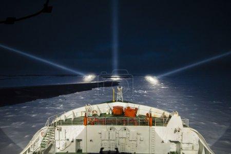 Photo pour Navire brise-glace naviguant de nuit à l'aide de projecteurs de perçage nocturne dans la mer polaire - image libre de droit