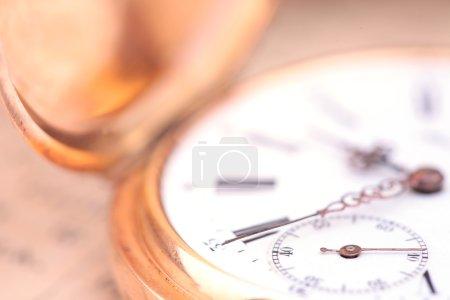 Foto de Closeup de reloj de bolsillo Oro vintage antiguo sobre un fondo de texto antiguo - Imagen libre de derechos