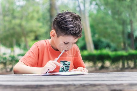 Boy learns to read and write at the park. Summer school holidays