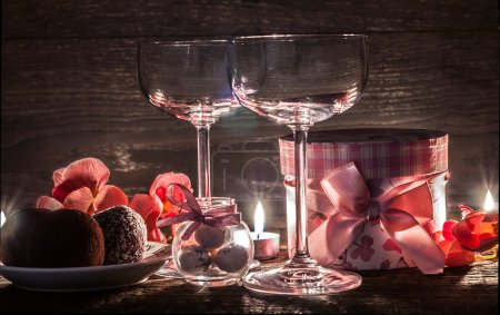 Photo for Wine glasses, gift and sweets on the table for a romantic evening - Royalty Free Image