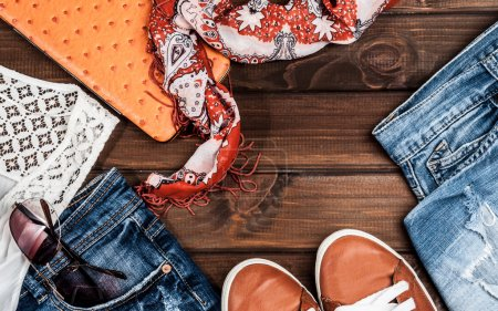 Jeans and fashion accessories on wooden boards...