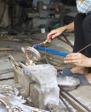 Junior craftsman making copper handicraft products