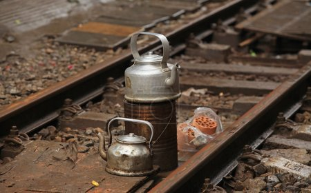 metal teapots on railroad lines