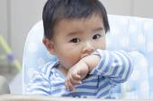 Cute Chinese baby boy sitting in baby chair