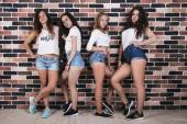 Four young girls in white t-shirts and jeans shorts standing nea