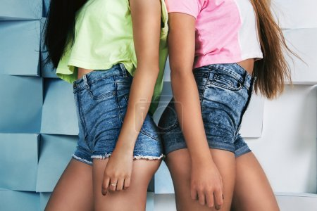 Two young fit girls in high waistline jeans shorts and bright co