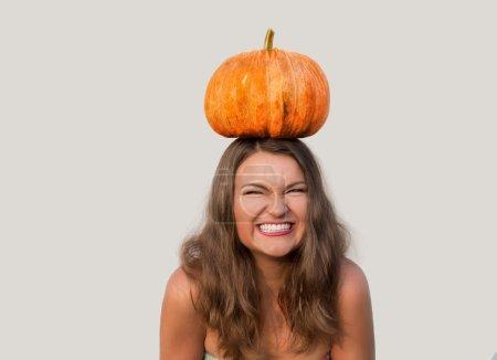 Photo pour Gloussant belle fille avec halloween citrouille sur sa tête sur fond blanc - image libre de droit
