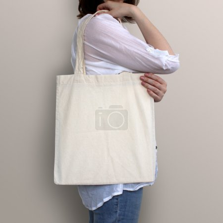 Girl is holding blank cotton eco bag, design mockup.