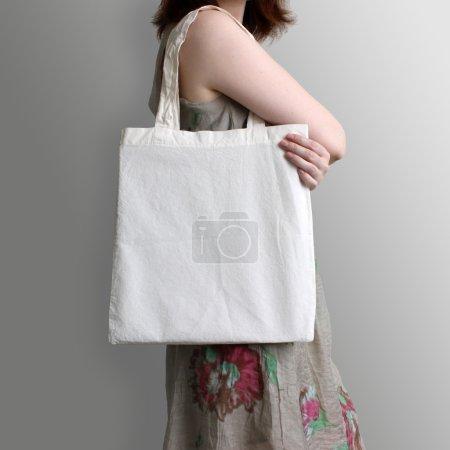 Photo pour Fille est tenir le sac cabas en coton blanc eco, conception de maquette. Sac à provisions à la main pour les filles. - image libre de droit
