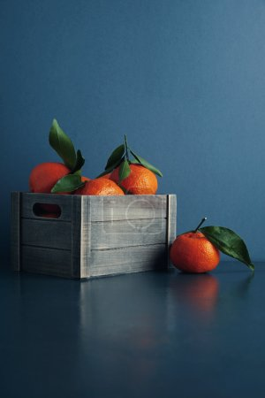 fresh tangerines in box with leaves isolated