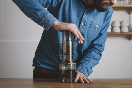 Bearded barista press aeropress to fill glass