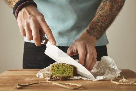 Tattooed hands slice green healthy bread